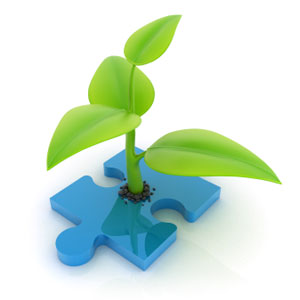 green plant growing from a missing jigsaw piece